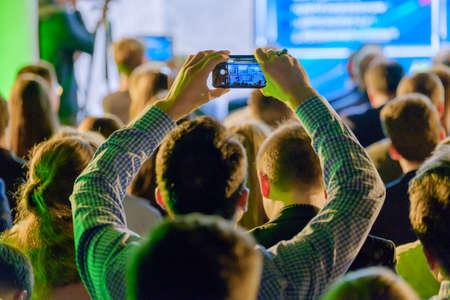 男は、スマート フォンを使用して、会議ホールでプレゼンテーションの写真を撮る
