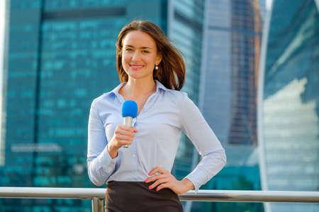 Jonge meid TV-reporter is uitzending op de moderne stadsachtergrond