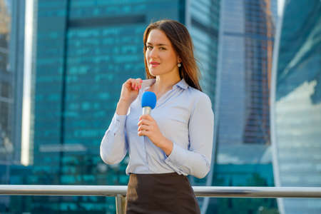 newsreader: Young girl TV reporter is broadcasting on modern city background Stock Photo