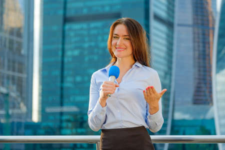 showreel: Young girl TV reporter is broadcasting on modern city background Stock Photo
