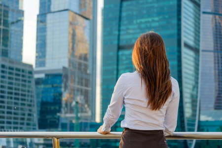 Young business woman looking to the modern business district