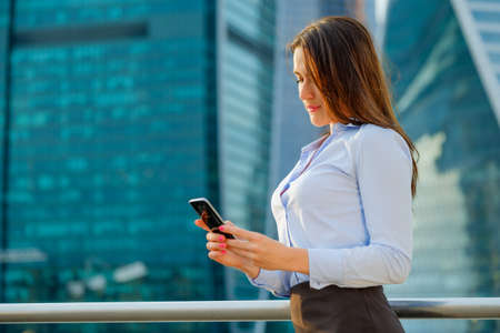 Young sexy business woman with smart phone on the modern city background portrait Stock Photo - 87279444