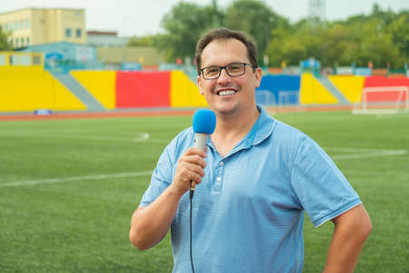 showreel: Middle age man TV reporter is broadcasting from stadium Stock Photo