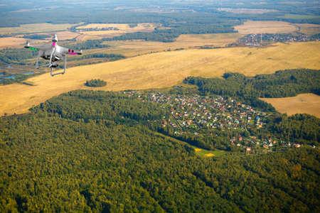 Quadrocopter flying over farmland at fall