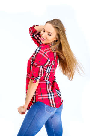 Young sexy woman dressed in jeans and checkered shirt posing in studio isolated on white Stock Photo