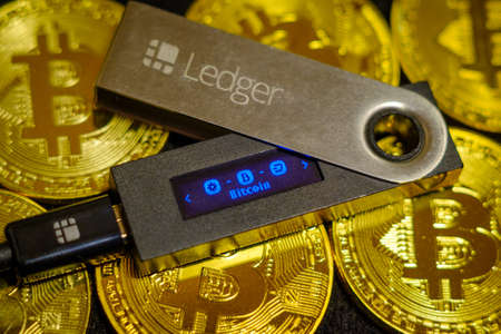 Moscow, Russia - September 8, 2017: Cold crypto wallet Ledger Nano S lying on golden bitcoin coins Editöryel