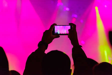 Concert visitor shoots video on a smartphone Stock Photo