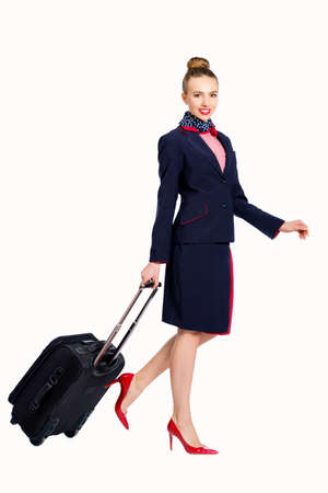 Young woman stewardess dressing uniform posing in studio isolated on white