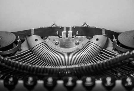 Typewriter ready for use with blank paper installed macro black and white background