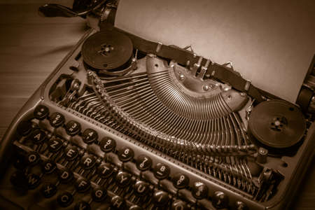 Typewriter ready for use with blank paper installed macro black and white background. Top view. Sepia tone