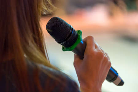 Speaker at conference holding microphone in the hand Stock Photo