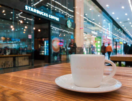 Moscow, Russia - May 10, 2017: Starbucks cafe interior in the Columbus mall, cup with logo at foreground