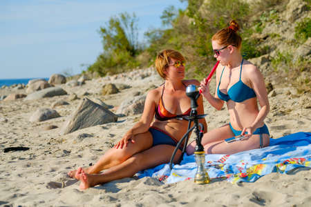 Two young girls smoking a hookah on the sandy beach Stock Photo