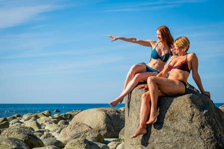 Two young women posing on the stony beach Фото со стока