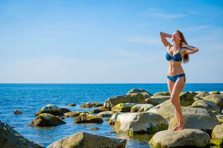 Young woman posing on the stony beach Standard-Bild