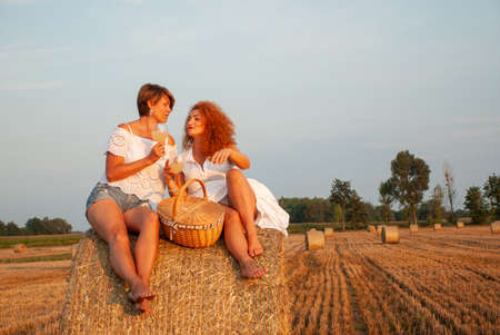 Two attractive women have picnic drink white vine and having fun on a haystack Stock fotó