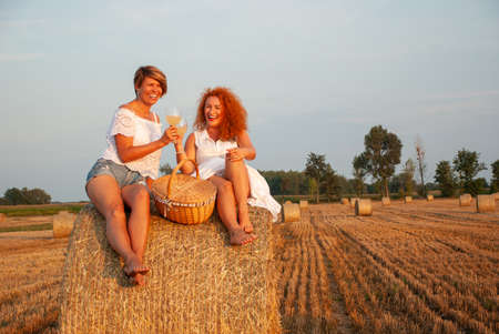 Two attractive women have picnic drink white vine and having fun on a haystack Stock Photo