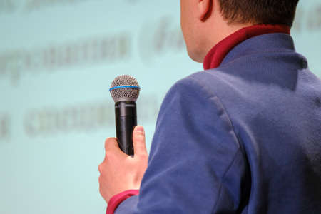 Man speaks, holding a microphone in his hand