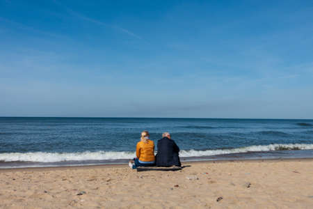 Svetlogrsk, Russia - May 8, 2018: Elderly couple sitting on the sea shore , rear view