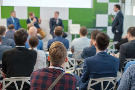 Publiczność słucha wykładowcy na konferencji biznesowej, widok z tyłu