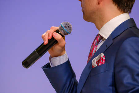 Adult caucasian male businessman in suit lecturer speech holding microphone in hand at business conference Reklamní fotografie