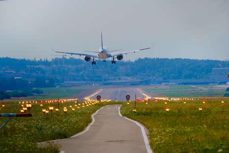Airplane landing at airport runway, back view