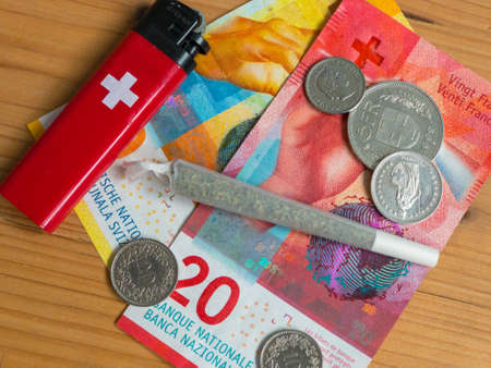 Swiss franc banknotes, lighter and joint with marijuana. flat lay, top view