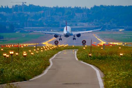 Airplane landing at airport runway, back view Фото со стока