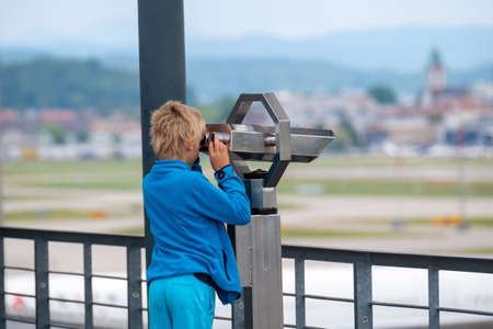 Boy looks through sights with public coin operated binoculars