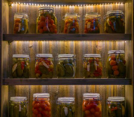 Pickles in jars on wooden shelves in pantry Reklamní fotografie