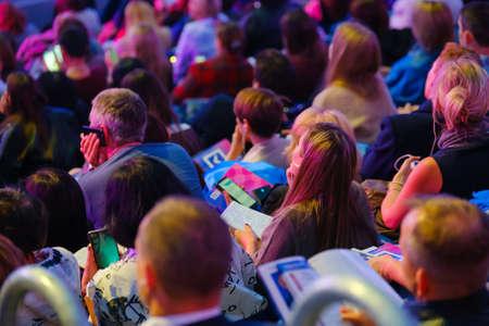 Teilnehmer von Geschäftskonferenzen sitzen und hören dem Dozenten zu, Ansicht von hinten