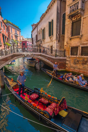 Venice, Italy - August 3, 2019: Gandolier riding tourists on gondola at sunny summer day