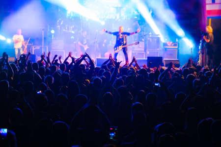 Fans en el concierto de música rock en vivo animando a los músicos en el escenario, vista posterior Foto de archivo
