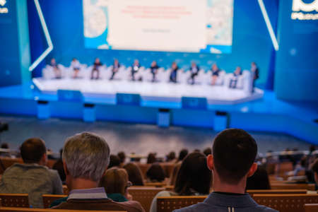 People attend business conference in large congress hall