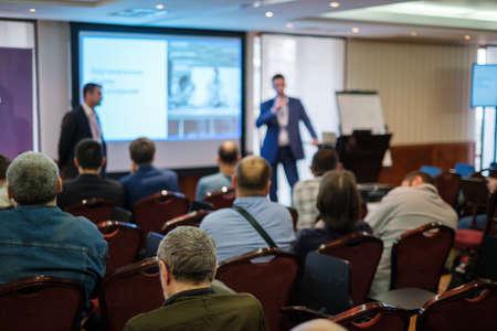 Publiek luistert docent op workshop in conferentiezaal, achteraanzicht