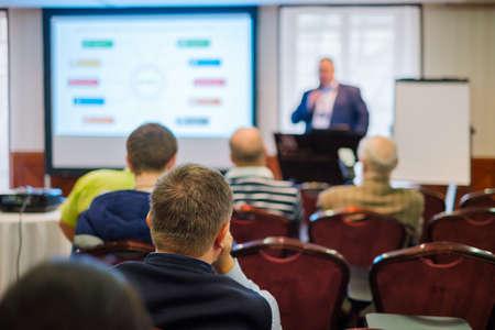 Publiczność słucha wykładowcy na warsztatach w sali konferencyjnej, widok z tyłu