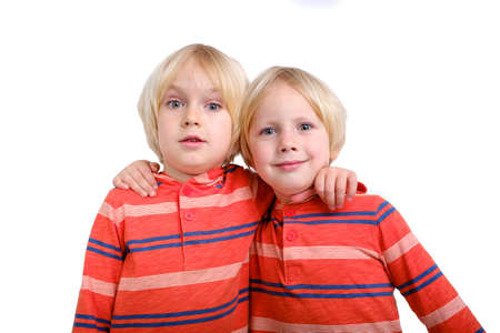 Two caucasian boys brothers posing in studio on white