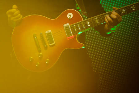 Guitarist playing electric guitar at live concert in night club 写真素材