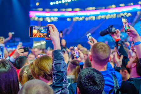 Audience at event uses smartphone camera to take photos and videos and live broadcasts 写真素材