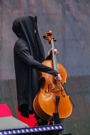Man in a black robe with hood plays the cello 写真素材