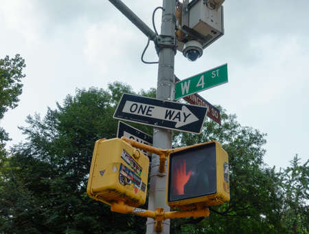 New York, USA - September 6, 2018: Low angle of post with red traffic light and road signs against green tree and cloudy sky on street of Manhattan in New York city