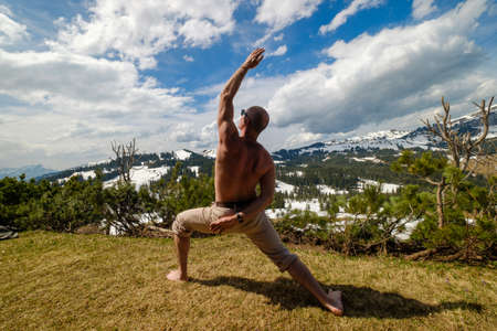 Back view of unrecognizable shirtless male lunging while doing yoga on lawn against snowy mountain range and cloudy sky in Switzerland