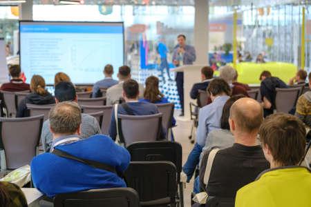 Teilnehmer von Geschäftskonferenzen sitzen und hören dem Dozenten in der modernen Halle zu, Rückansicht Standard-Bild