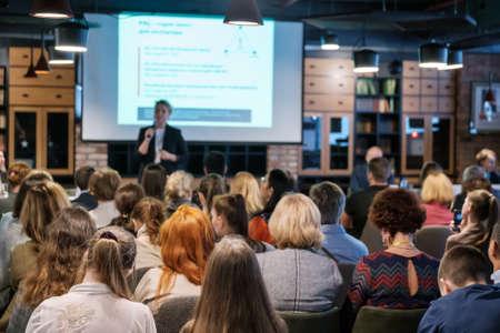 Publiek luistert docent bij workshop in conferentiezaal