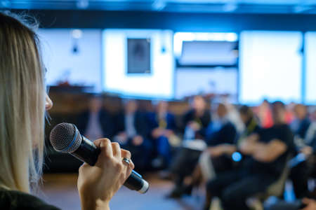 Female presenter speaks to audiences at conference