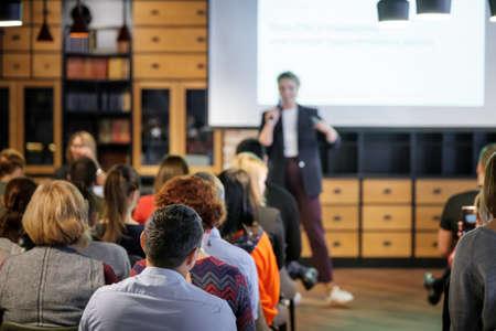 Publiczność słucha wykładowcy na warsztatach w sali konferencyjnej