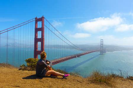 Junge glückliche Frau sitzt und posiert fot Fotograf auf dem Hintergrund der Golden Gate Bridge am sonnigen Tag, San Francisco, Kalifornien, USA
