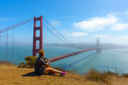 Young happy woman sitting and posing fot photographer on background of Golden Gate Bridge at sunny day, San Francisco, California, USA