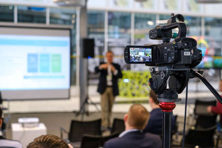 Video camera on tripod recording presentation of male coach standing on stage with display in front of audience