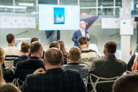 Audience listens lecturer at workshop in conference hall